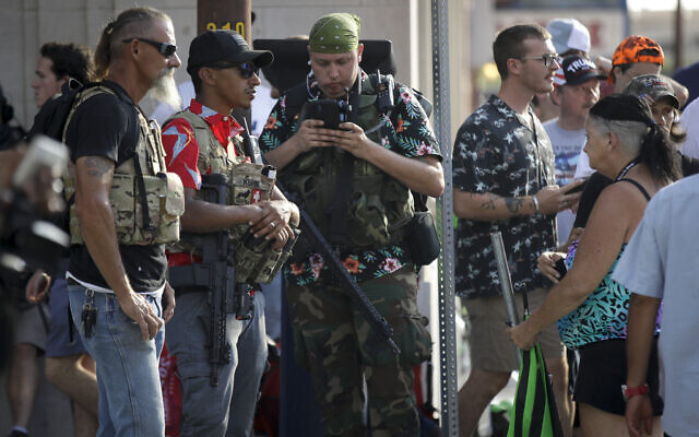 Illustrative: Gun-carrying men wearing the Hawaiian print shirts associated with the Boogaloo movement watch a demonstration near the BOK Center where US President Donald Trump will hold a campaign rally in Tulsa, Oklahoma, June 20, 2020. (AP Photo/Charlie Riedel)
