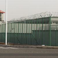 A guard tower and barbed wire fence surround a detention facility in the Kunshan Industrial Park in Artux, in western China's Xinjiang region, December 3, 2018. (AP Photo/Ng Han Guan, File)