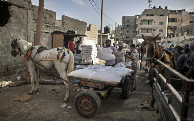 A Palestinian man loads a horse cart with sacks of flour received from the UN Relief and Works Agency (UNRWA), at a warehouse in Gaza City, September 30, 2020. (AP Photo/Khalil Hamra)