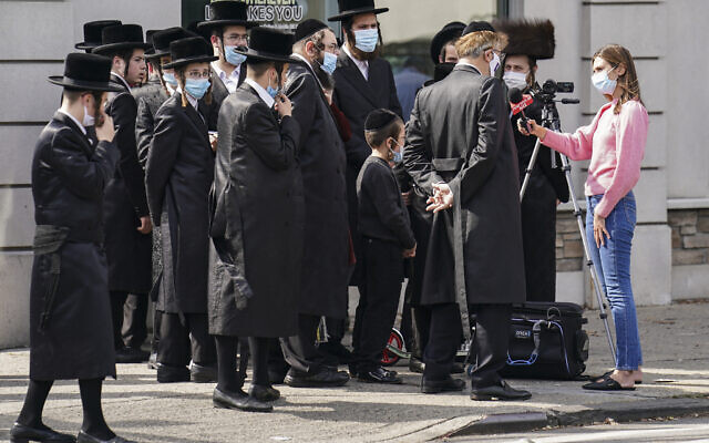 Members of ultra-Orthodox community gather to listen to an interview conducted by a journalist on a street corner, in the Borough Park neighborhood of New York as Gov. Andrew Cuomo moved to reinstate restrictions on houses of worship in and near areas where coronavirus cases are spiking, October 7, 2020. (John Minchillo/AP)