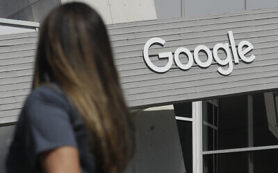 FILE - In this Sept. 24, 2019, file photo, a woman walks below a Google sign on the campus in Mountain View, Calif.  (AP Photo/Jeff Chiu, File)