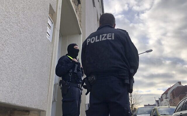 Illustrative: Police officers stand outside an apartment building during a search in Osnabrueck, Germany, November 6, 2020. (Festim Beqiri/TV7News/dpa via AP)