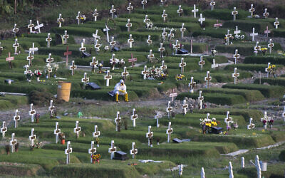 A worker in protective suits takes a break amid graves at a newly opened cemetery for the victims of COVID-19 in Medan, North Sumatra, Indonesia, November 16, 2020. (Binsar Bakkara/AP)