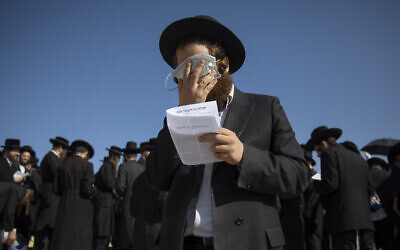 An ultra-Orthodox Jewish man covers his eyes with a face mask in Jerusalem, November 18, 2020. (AP/Oded Balilty)