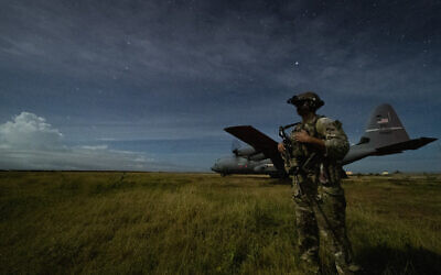 A junior sniper, assigned to the 1-186th Infantry Battalion, Task Force Guardian, Combined Joint Task Force - Horn of Africa, provides security for a 75th Expeditionary Airlift Squadron (EAS) C-130J Super Hercules during unloading operations at an unidentified location in Somalia June 28, 2020 (Tech. Sgt. Christopher Ruano/Combined Joint Task Force - Horn of Africa via AP)
