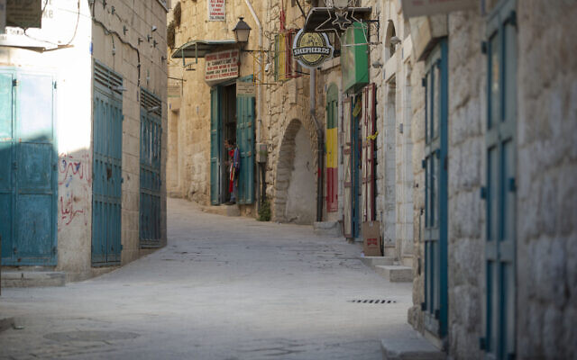 A Palestinian vendor stands in front of his shop near the Church of the Nativity, traditionally believed to be the birthplace of Jesus Christ, in the West Bank City of Bethlehem, Monday, Nov. 23, 2020. (AP Photo/Majdi Mohammed)