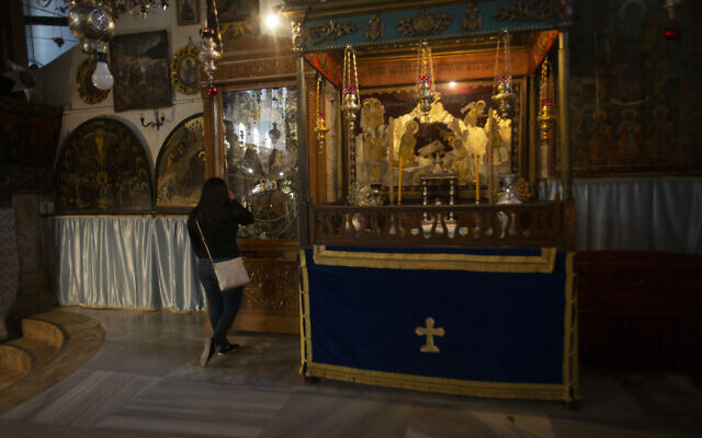 Christian worshipper prays in the Church of the Nativity, traditionally believed to be the birthplace of Jesus Christ, in the West Bank city of Bethlehem, Monday, Nov. 23, 2020.  (AP Photo/Majdi Mohammed)