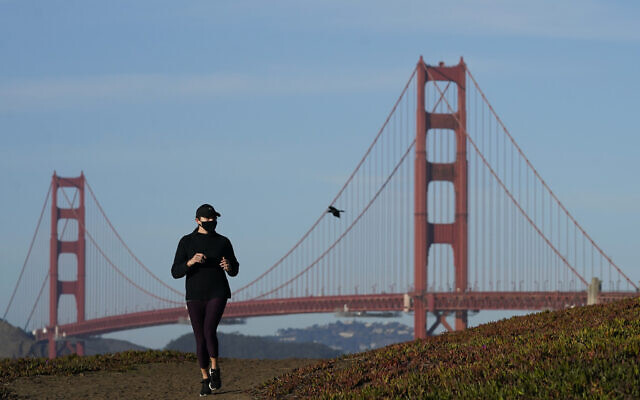 A person wearing a mask runs on a path in front of the Golden Gate Bridge during the coronavirus pandemic in San Francisco, Monday, Nov. 30, 2020. (AP Photo/Jeff Chiu)