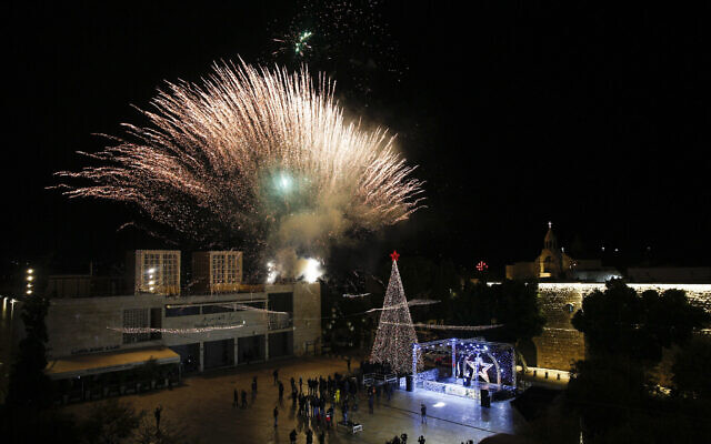 Palestinian Christians attend the lighting of a Christmas tree outside the Church of the Nativity, traditionally believed by Christians to be the birthplace of Jesus Christ in the West Bank city of Bethlehem, Saturday, Dec. 5, 2020. (AP Photo/Majdi Mohammed)