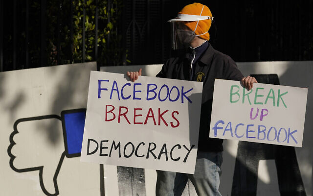 A demonstrator joins others outside Facebook CEO Mark Zuckerberg's home in San Francisco to protest what they say is Facebook spreading disinformation, November 21, 2020. (AP Photo/Jeff Chiu, File)