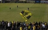 Beitar Jerusalem soccer supporters sing and wave their flag as players enter the pitch during a team training session in Jerusalem, Friday, Dec. 11, 2020, days after the club announced that an Emirati sheikh has purchased a 50% stake in the team (AP Photo/Maya Alleruzzo)