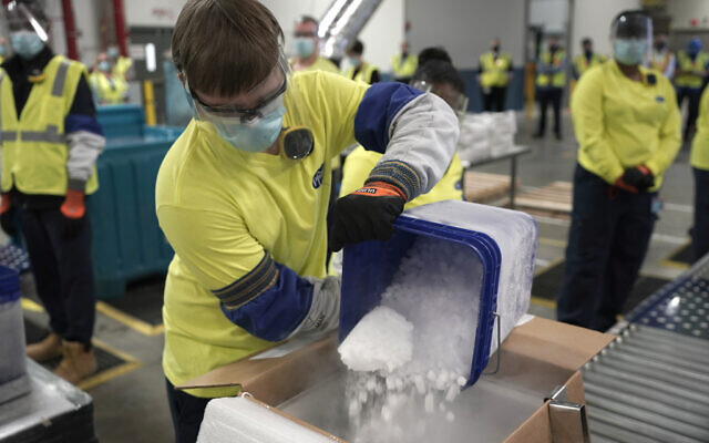 Dry ice is poured into a box containing the Pfizer-BioNTech COVID-19 vaccine as it is prepared to be shipped at the Pfizer Global Supply Kalamazoo manufacturing plant in Portage, Michigan, Dec. 13, 2020. (AP Photo/Morry Gash, Pool)