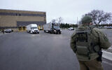 A US marshal watches as trucks loaded with the Pfizer-BioNTech COVID-19 vaccine leave the Pfizer Global Supply Kalamazoo manufacturing plant in Portage, Michigan, December 13, 2020. (Morry Gash/AP)