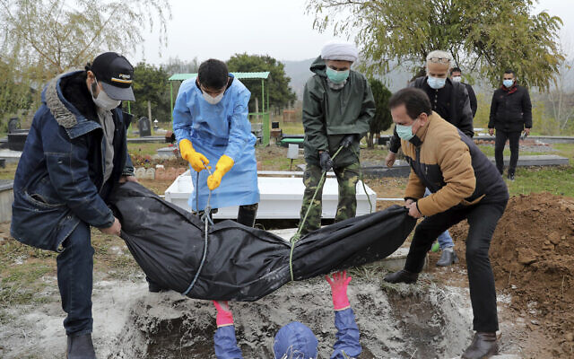 Volunteers and relatives wearing protective clothing and masks lower the body of a man who died from COVID-19 into a grave at a cemetery in the outskirts of the city of Ghaemshahr, in northern Iran, Dec. 18, 2020. (AP Photo/Ebrahim Noroozi)
