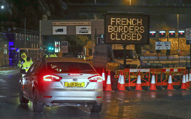 Police and port staff turn away a vehicle from the Port of Dover in Kent, England, which has been closed after France banned entry from the United Kingdom for 48 hours due to a new strain of the coronavirus, December 21, 2020. (Steve Parsons/PA via AP)