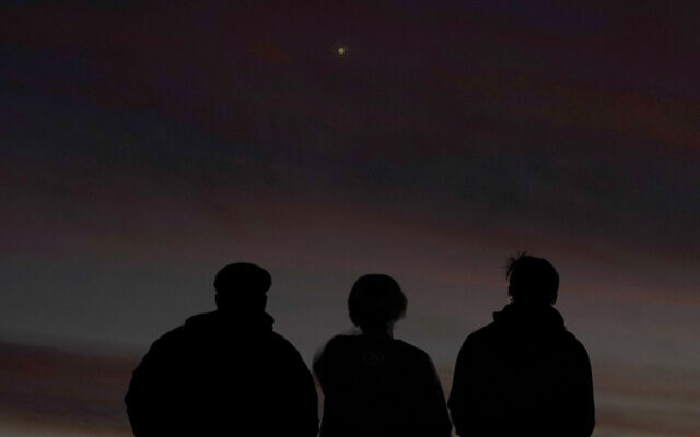People are silhouetted against the sky at dusk as they watch the alignment of Saturn and Jupiter, December 21, 2020, in Edgerton, Kansas. (AP Photo/Charlie Riedel)