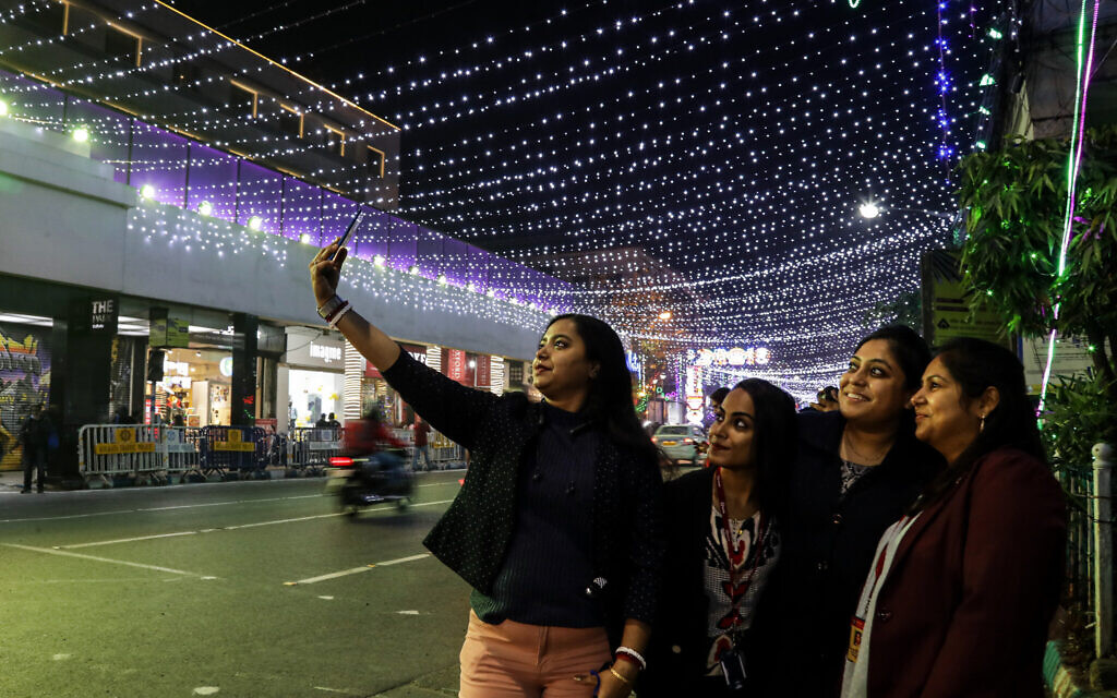 A group of Indian women take a selfie on a mobile phone in a street decorated ahead of Christmas in Kolkata, India, Tuesday, December 22, 2020. (AP Photo/Bikas Das)