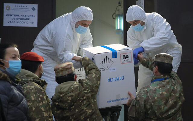 Men wearing full protective suits against coronavirus, take a box containing COVID-19 vaccines, from military personnel at the National Center for Storage of the COVID-19 Vaccine, a military run facility, in Bucharest, Romania, Dec. 26, 2020 (AP Photo/Vadim Ghirda)