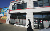 An Orthodox Jewish man walks past Parcare's health care facility, December 27, 2020, in the Willamsburg section of Brooklyn in New York. (AP Photo/Kathy Willens)