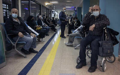 People wait to receive a Pfizer COVID-19 vaccine in Soroka Hospital in Beersheba, December 29, 2020 (AP Photo/Tsafrir Abayov)