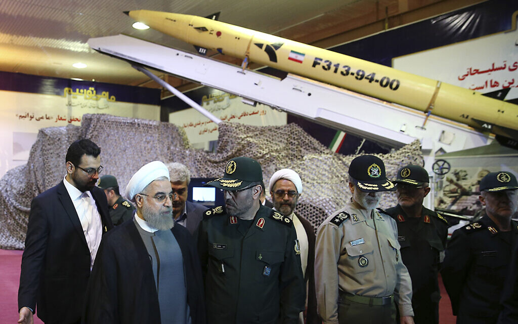 Iran's President Hassan Rouhani, second left, speaks with then Defense Minister Hossein Dehghan after unveiling the surface-to-surface Fateh-313, or Conqueror, missile in a ceremony marking Defense Industry Day, August 22, 2015. (Iranian Presidency Office via AP)