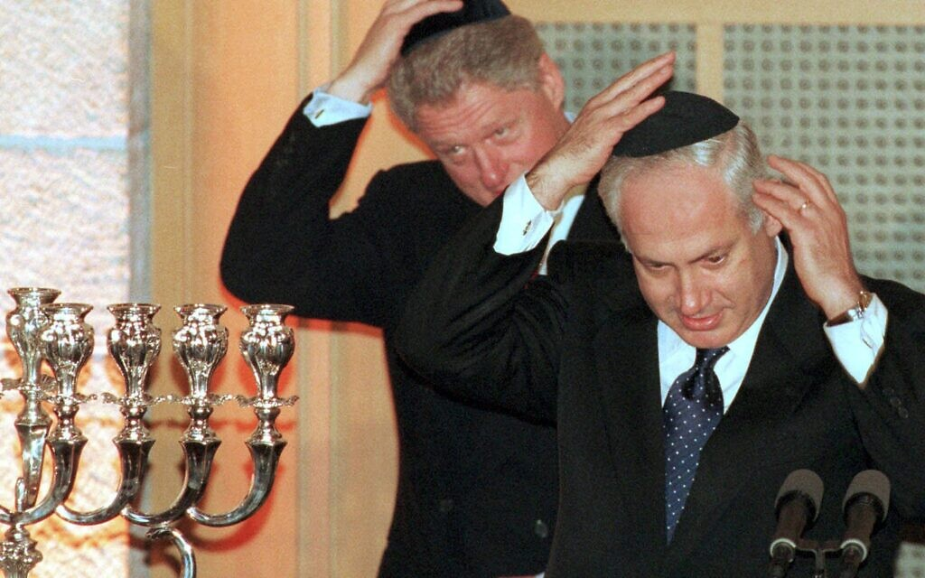 Prime Minister Benjamin Netanyahu and President Clinton put on yarmulkes before lighting a Hanukkah candle during a state dinner held on December 13, 1998, in Jerusalem, in honor of the visiting president. (AP/Zoom 77)