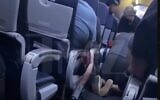 Screen capture from video showing passengers performing CPR on a man who collapsed with possible COVID-19 symptoms while on a United Airlines flight, December 14 2020. (YouTube)