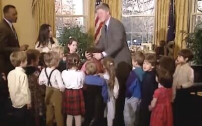 Screen capture from 1993 video showing US President Bill Clinton grabbing Ilana Kattan's hair to stop it from burning after noticing that it had caught fire on the menorah her class had just helped him light at the White House. (Clinton Presidential Library on YouTube via JTA)