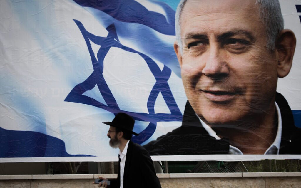 An ultra-Orthodox man walks near an election campaign poster showing Benjamin Netanyahu in Jerusalem on April 2, 2019. (Yonatan Sindel/Flash90)