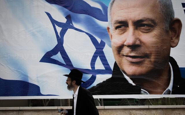 An ultra-Orthodox man walks near an election campaign poster showing Benjamin Netanyahu in Jerusalem on April 2, 2019. (Yonatan Sindel/Flash90)