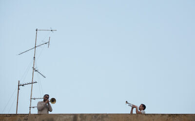 Israelis listen from their balconies as saxophonist Yarden Klayman performs a concert from a rooftop on Basel Square, in Tel Aviv, March 23, 2020. (Miriam Alster/Flash90)
