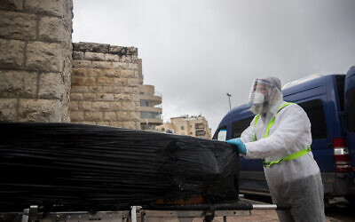 Chevra Kadisha workers wearing protective clothing carry the body of a patient who died from complications of COVID-19 at the Shamgar Funeral Home in Jerusalem on April 1, 2020 (Yonatan Sindel/Flash90)
