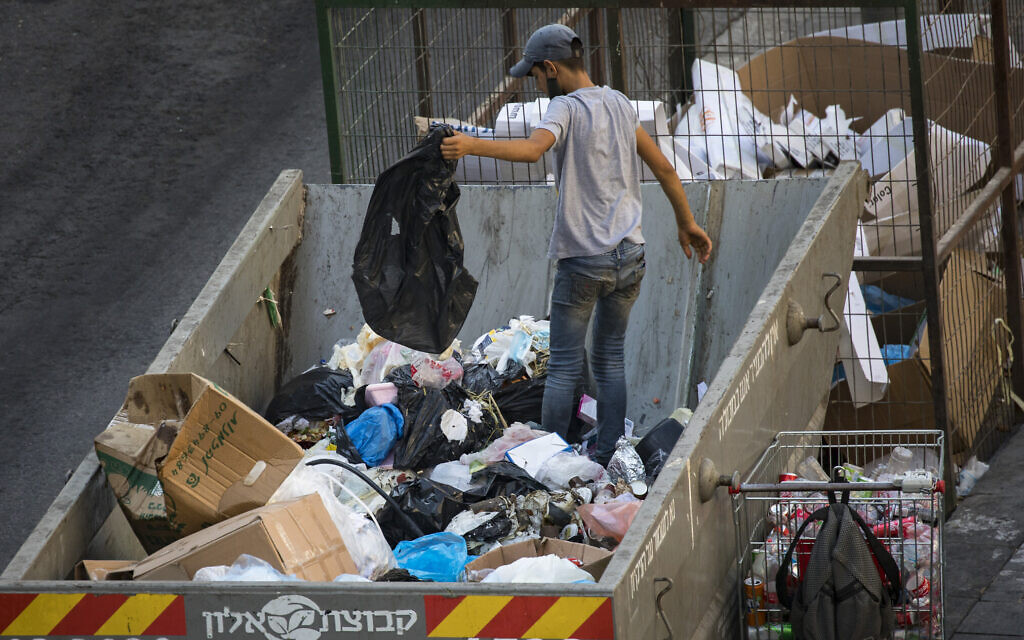 A teenager search for cans through a garbage container in the center of Jerusalem on September 02,2020. (Nati Shohat/Flash90)