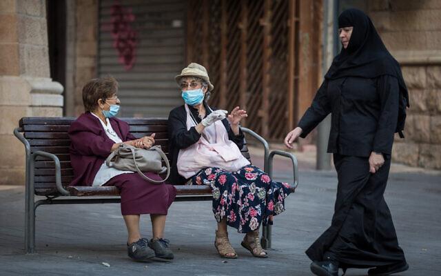 Two elderly women sit on a bench on Jaffa Street in downtown Jerusalem on October 26, 2020. (Nati Shohat/Flash90)