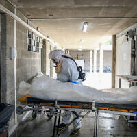 Illustrative: Workers prepare a body before a funeral ceremony at a morgue for coronavirus victims, in Holon, on October 28, 2020. (Flash90)