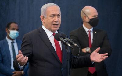 Prime Minister Benjamin Netanyahu, center, during a visit at the coronavirus national enforcement administration in Tel Aviv, December 01, 2020. (Miriam Alster/FLASH90)