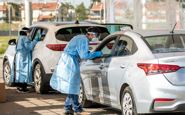 Health care workers take test samples of Israelis in a drive through complex to check if they have been infected with the Coronavirus in a mobile testing station, in Lod, on December 1, 2020. (Yossi Aloni/Flash90)