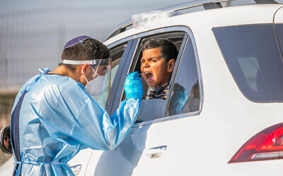 Healthcare workers take test samples from Israelis to check if they have been infected with the coronavirus in Lod, on December 1, 2020. (Yossi Aloni/Flash90)