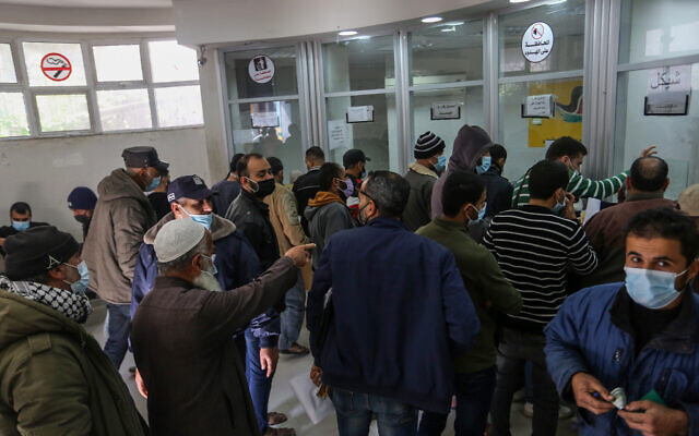 Palestinians receive their $100 financial aid as part of the aid allocated by Qatar to poor families, through a post office, in the town of Khan Yunis, southern Gaza Strip, on December 3, 2020. (Abed Rahim Khatib/Flash90)