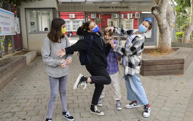 Illustrative: Israeli students wearing face masks return to high school in Tel Aviv on December 6, 2020. (Avshalom Sassoni/ Flash90)