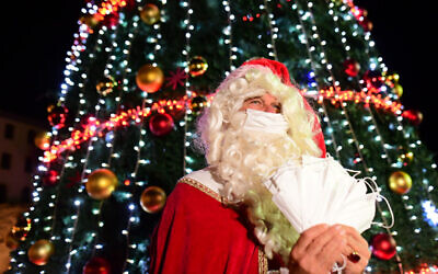 A man dressed as Santa Claus seen during the annual Christmas tree lighting ceremony in Jaffa, December 6, 2020 (Tomer Neuberg/Flash90)