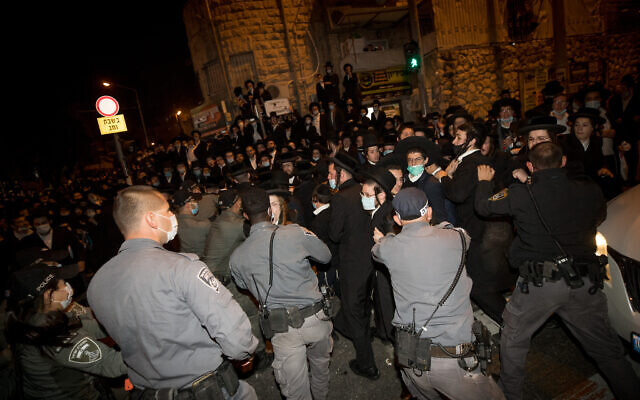 Ultra-Orthodox Jewish men scuffle with Israeli police as they protest against the new contractions work for the Jerusalem Light Rail, December 7, 2020. (Yonatan Sindel/Flash90)