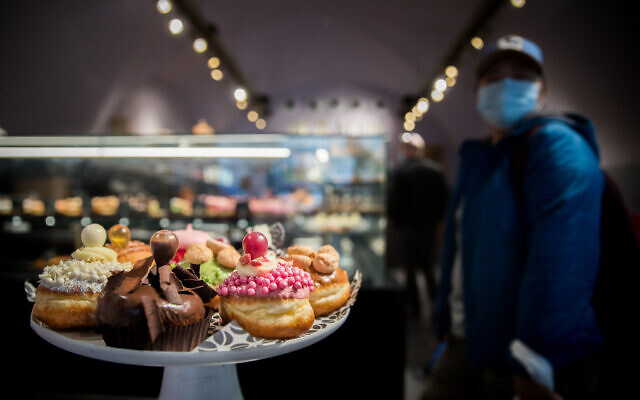 Israeli donuts sold at the Roladin bakery ahead of the Jewish holiday of Hanukkah, outside the Mahane Yehuda market in Jerusalem, on December 7, 2020. (Yonatan Sindel/Flash90)