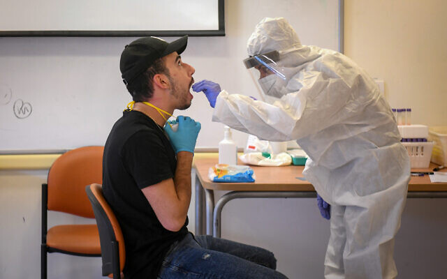 Health care workers take coronavirus test samples at a testing center, in Rishon Lezion on December 8, 2020. (Flash90)