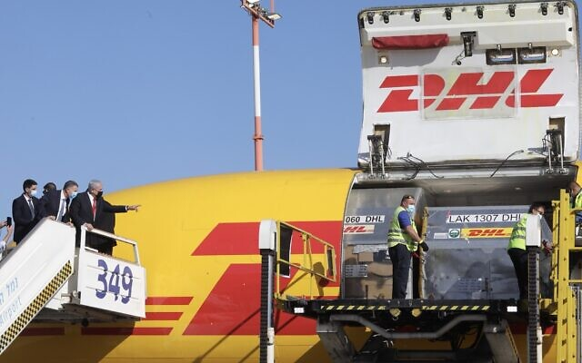 Prime Minister Benjamin Netanyahu and Health Minister Yuli Edelstein attend the arrival of a DHL freight plane transporting the first batch of Pfizer vaccines at Ben Gurion Airport on December 9, 2020. (Marc Israel Sellem/Pool)