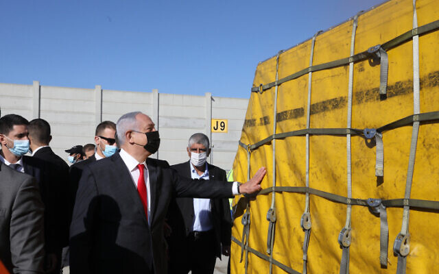Prime Minister Benjamin Netanyahu touches the first batch of Pfizer vaccines to arrive in Israel at Ben Gurion Airport near Tel Aviv, December 9, 2020. (Marc Israel Sellem/Pool)