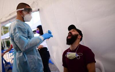 Health care workers test Israelis for coronavirus at Rabin Square in Tel Aviv on December 10, 2020. (Tomer Neuberg/Flash90)