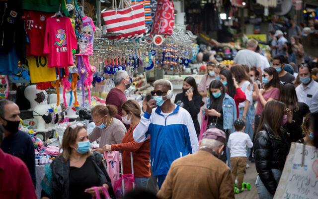People wear protective masks at the Carmel market in Tel Aviv, on December 13, 2020. (Miriam Alster/FLASH90)