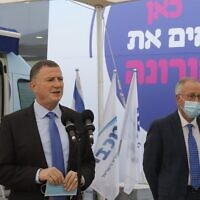 """Health Minister Yuli Edelstein gives a press conference at a coronavirus vaccine center in Tel Aviv on December 13, 2020. The slogan behind him reads: """"Here, we're beating coronavirus."""" At right is Maccabi health fund head Ran Saar. (Marc Israel Sellem/Flash90/Pool)"""