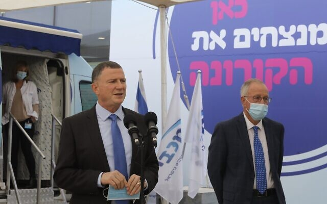"Health Minister Yuli Edelstein gives a press conference at a coronavirus vaccine center in Tel Aviv on December 13, 2020. The slogan behind him reads: ""Here, we're beating coronavirus."" At right is Maccabi health fund head Ran Saar. (Marc Israel Sellem/Flash90/Pool)"